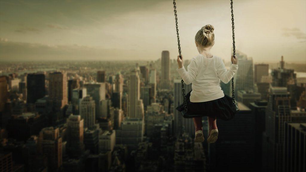 dziewczynka na huśtawce na tle miasta